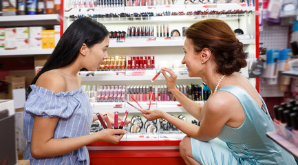 Cheerful girl with mother choosing new lipstick
