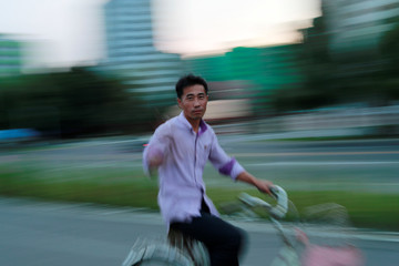 A man rides a bicycle along the Taedong river in Pyongyang