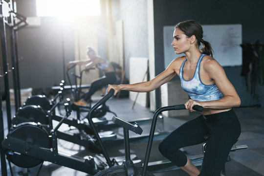 Sport Workout At Gym. Woman Training On Crossfit Bicycle