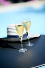 two glass of cool champagne wine outdoor in a restaurant pool side terrace in sunny summer day