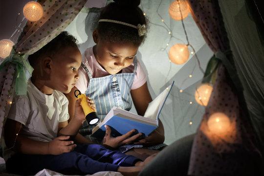Little African-American children reading bedtime story in hovel