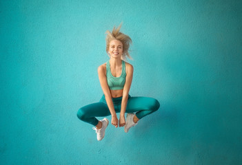 Sporty woman jumping near color wall
