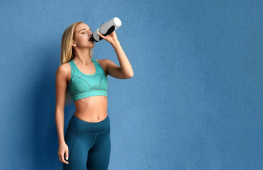 Sporty woman with bottle of water near color wall