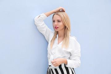 Beautiful young woman posing near color wall