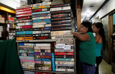 Residents buy second-hand pocket books in a shop at the University Belt in Manila