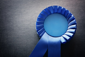 Blue award rosette with ribbons and copy space