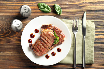 Plate with delicious grilled steak and sauce on wooden table