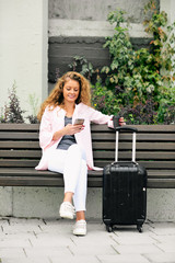 Portrait of woman suing smart phone while siting on the bench on the station. Next to her luggage.