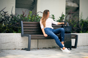 Woman waiting on the bus station and sitting on bench.Next to her luggage. In hand coffee to go.