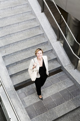 Smiling businesswoman walking downstairs
