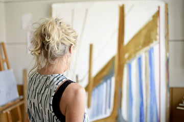 Female painter in her atelier,  looking on painting