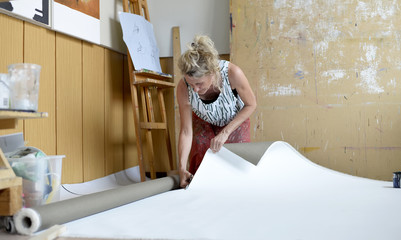 Female painter in her atelier, cutting paper