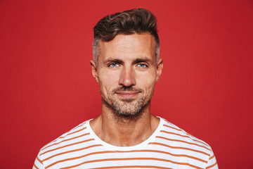 Adult attractive man with stubble in striped t-shirt smiling on camera, isolated over red background Fototapete
