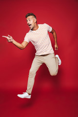 Full length photo of adult man in striped t-shirt running and screaming, isolated over red background