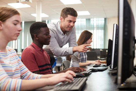 Teacher Helping Male High School Student Working In Computer Class