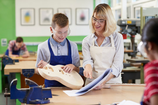 Female Teacher Helping Male High School Student Building Guitar In Woodwork Lesson