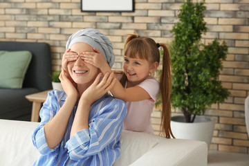 Little girl playing with her mother after chemotherapy at home