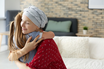 Woman after chemotherapy hugging her daughter at home