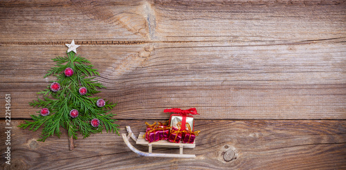 Christmas Tree On Wooden Board With A Sleigh Loaded With Christmas