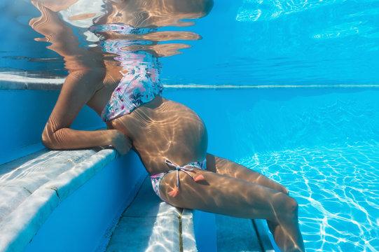 Schwangere Frau sitzt in einem Pool; Unterwasseraufnahme