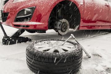 Winterreifenwechsel im Schnee während es schneit