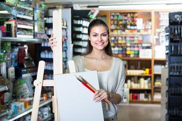 woman choosing canvas on easel