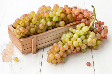 A bunch of juicy ripe grapes in a small wooden box on an old table.
