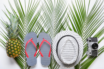 Summer composition with fresh tropical palm leaves, pineapple and beach accessories on white background