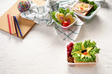 Lunch boxes with appetizing sandwiches on white textured background