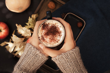 Female  holding cup of pumpkin spice latte coffee, Autumn fall mood, holding hands, top view , warm and cozy. Copy space.
