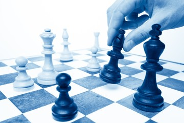 A Hand Holding a Chess Piece on a Chessboard