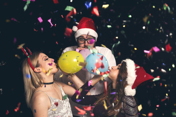Friends blowing balloons at New Year's party
