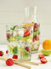 Glasses of fresh strawberry lemonade on light wooden table