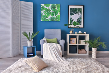 Stylish room interior with armchair and green tropical leaves