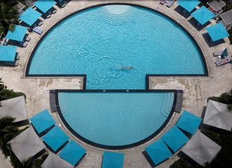 A man swims in a hotel pool in Singapore