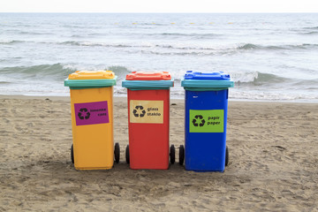 multi-colored containers for sorting garbage are on the beach against the sea