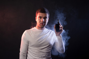 Man is smoking vape. Portrait in studio on a black background. Concept of tobacco dependence