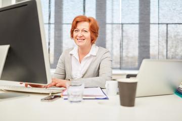 Seniorin arbeitet am Computer Arbeitsplatz