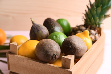 Crate with various delicious exotic fruits on color table