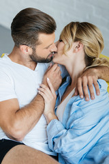 beautiful passionate young couple in love kissing at home