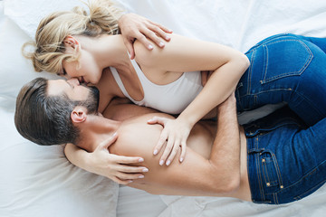top view of sexy young couple in jeans hugging and kissing on bed