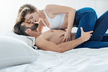 side view of passionate young couple hugging and kissing in bed