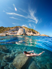 "Half underwater with girl diving on a beautiful sea with granite cliff. Villasimius ""Cava Usai"", Sardinia."