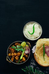 Kerala Pork Fry or Roast served with Parotta and rice on black background