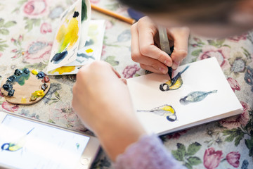 Teenager girl drawing bird in small paper drawing-pad. Close-up kid artist painting small picture on paper notepad with brush. Children creativity concept