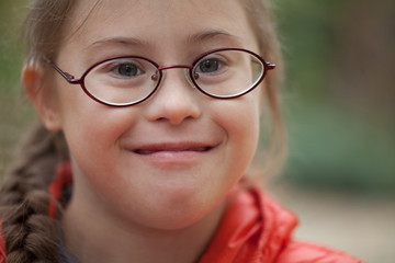 Portrait of a girl with special needs in glasses close-up