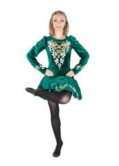 Beautiful young woman in Irish dance green dress jumping isolated