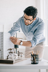 handsome architect working with architecture model on table in office