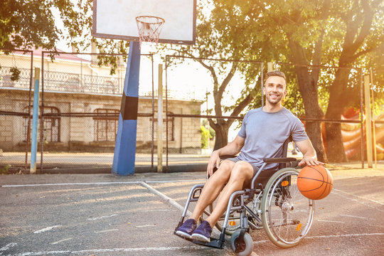 Young man in wheelchair playing basketball outdoors