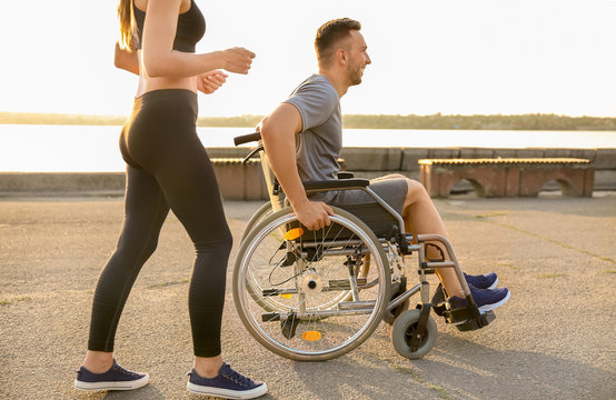 Young man in wheelchair and sporty woman training outdoors